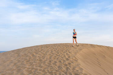 Woman running in the dunes, Gran Canaria, Spain - DIGF12575