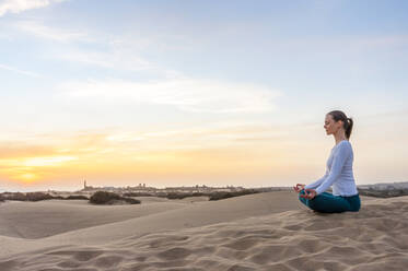 Woman practicing yoga at sunset in the dunes, Gran Canaria, Spain - DIGF12578