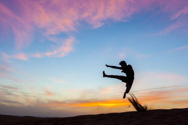 Silhouette of man jumping at sunset in the dunes, Gran Canaria, Spain - DIGF12584