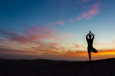 Silhouette of man doing yoga at sunset, Gran Canaria, Spain - DIGF12587