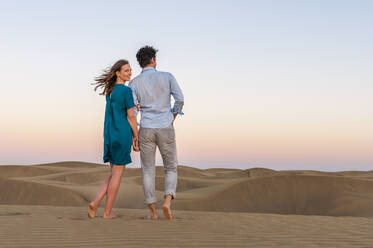 Affectionate couple walking in the dunes at sunset, Gran Canaria, Spain - DIGF12596