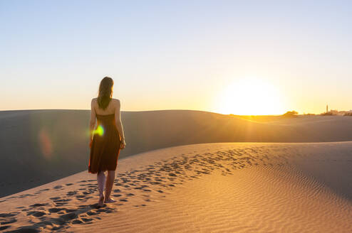 Woman in red dress at sunset in the dunes, Gran Canaria, Spain - DIGF12605