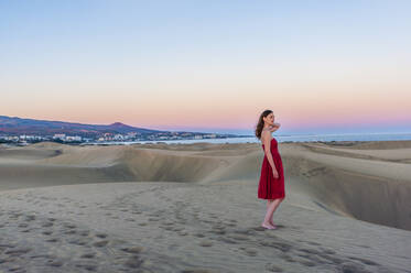 Woman in red dress at sunset in the dunes, Gran Canaria, Spain - DIGF12608