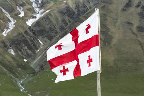 Georgia, Svaneti, Ushguli, Georgian national flag fluttering outdoors - WVF01724