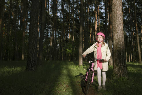 Girl standing with bicycle in forest - EYAF01083