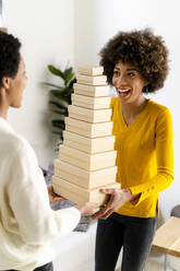 Portrait of laughing young woman balancing stack of boxes - GIOF08275