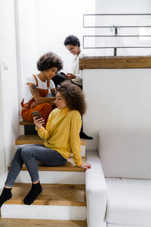 Three friends sitting on stairs at home using their smartphones - GIOF08299