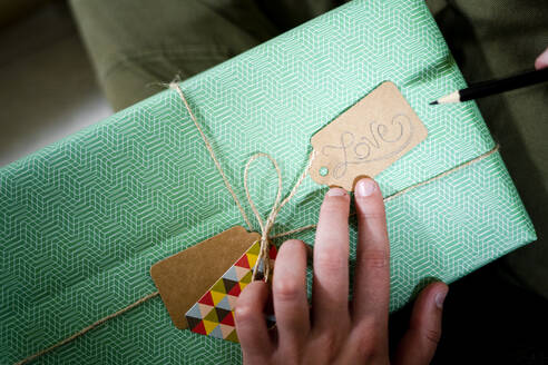 Hand holding tag with the word 'Love' on wrapped gift - GIOF08323