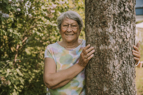 Smiling active senior woman standing by tree against plants at garden - MFF05866