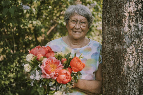 Senior woman holding fresh peony bouquet by tree trunk at garden - MFF05869