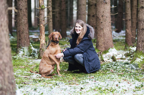 Smiling young beautiful woman crouching by dog against trees in forest - DIGF12653