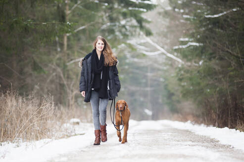 Beautiful young woman walking with dog on road amidst trees in forest during winter - DIGF12659