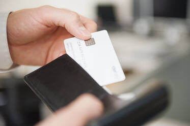 Hands of man holding wallet and blank white credit card - DIGF12668
