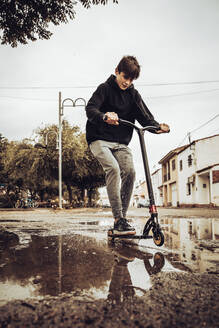 Teenage boy riding push scooter in puddle on street against sky - ACPF00726