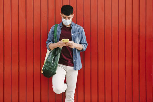 Man with protective mask and shopping bag looking at cell phone in front of red background - AGGF00069