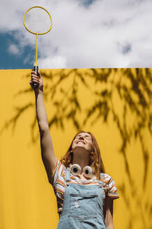 Happy young woman holding badminton racket over yellow wall during sunny day - AFVF06443