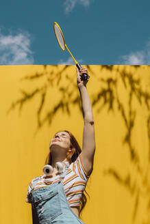 Young woman holding badminton racket over yellow wall during sunny day - AFVF06446