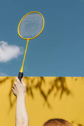 Woman's hand holding badminton racket over yellow wall against blue sky during sunny day - AFVF06452