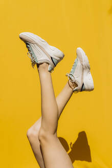 Woman's legs in sports shoes over yellow wall during sunny day - AFVF06458