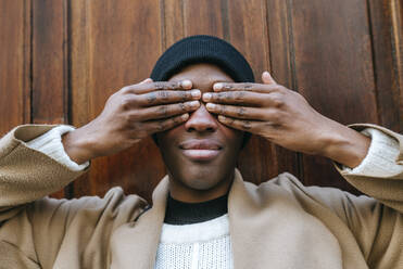 Young woman covering eyes with hands against wooden wall - KIJF03048