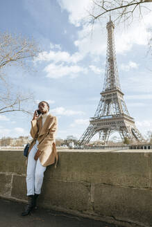 Woman using smart phone while standing on bridge with Eiffel Tower in background against sky, Paris, France - KIJF03060