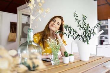 Smiling young woman with houseplants on table sitting at home during quarantine - AFVF06482