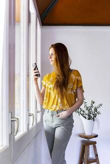 Young woman using smart phone while standing by window at home during curfew - AFVF06485