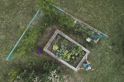 Aerial view of woman standing by raised bed on grassy land in yard - HMEF00949