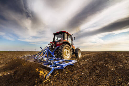 Farmer in tractor plowing agricultural land against cloudy sky - NOF00098