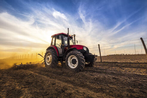 Man in tractor plowing agricultural land against cloudy sky - NOF00101
