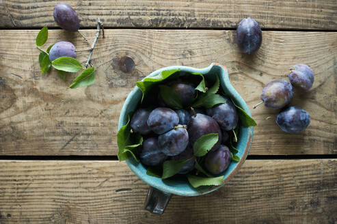 Jug of fresh plums standing on wooden surface - ASF06626