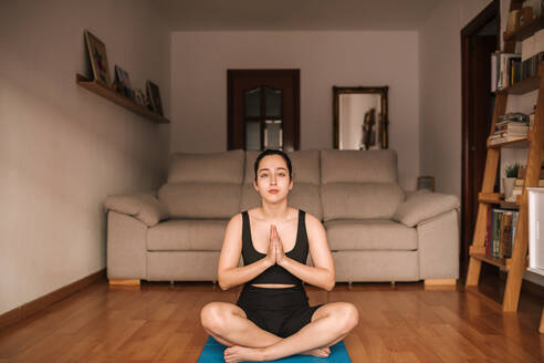 Confident woman meditating in prayer position at home - GRCF00261