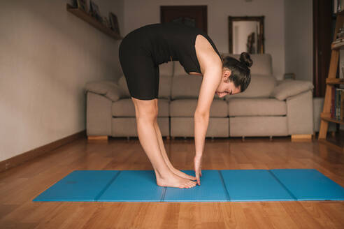 Young woman bending while practicing yoga in living room at home - GRCF00264
