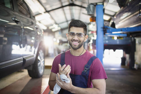 Portrait confident male mechanic wiping hands in auto repair shop - HOXF06426