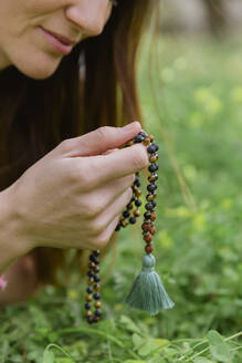 Close-up of mid adult woman holding beads meditating over grassy land - LVVF00001