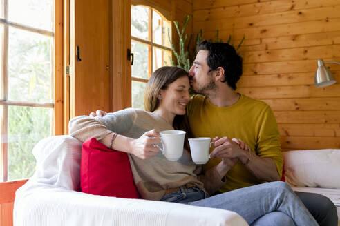 Romantic boyfriend holding coffee mug kissing on woman's forehead while sitting in log cabin - LVVF00004