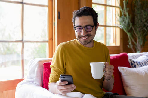 Smiling man holding coffee using smart phone while sitting on sofa in log cabin - LVVF00007