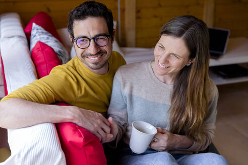 Smiling couple holding hands while relaxing on sofa in log cabin - LVVF00010