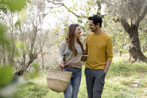 Romantic couple looking at each other while walking against trees in farm - LVVF00019