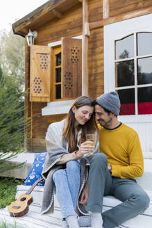 Romantic man sitting with girlfriend holding wineglass against log cabin - LVVF00052