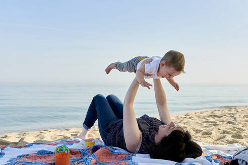 Mother picking up happy son while lying on blanket at beach against sea - JNDF00166