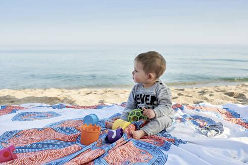 Cute boy with toys sitting on blanket at beach against sea - JNDF00169