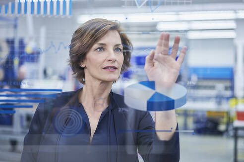 Female manager touching graph on glass in industry - RORF02184