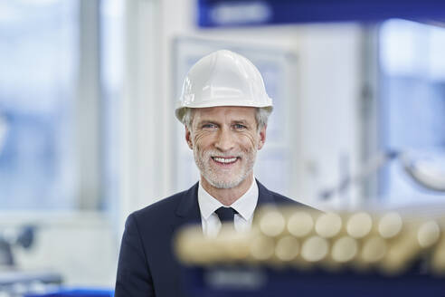 Happy mature male manager wearing white hardhat in factory - RORF02208