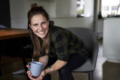 Smiling woman holding coffee mug looking away while sitting on chair at home - AUF00549