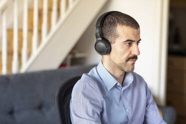 Businessman working from home, using headphones - WPEF02979