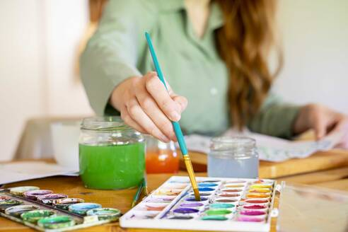 Young woman dipping paintbrush in watercolor on table at home - AFVF06495