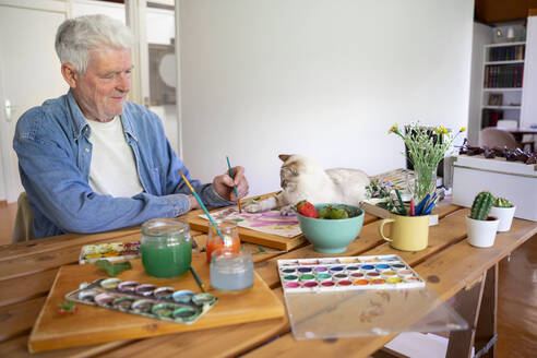 Senior man painting while cat lying on table at home - AFVF06513