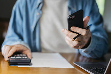 Senior man holding smart phone while using calculator and laptop at home - AFVF06544