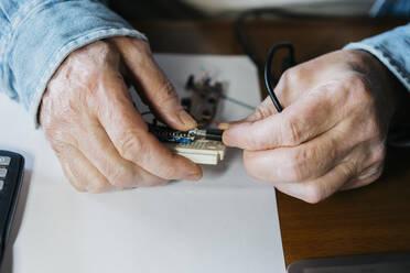 Cropped image of senior man repairing USB board of laptop at home - AFVF06547